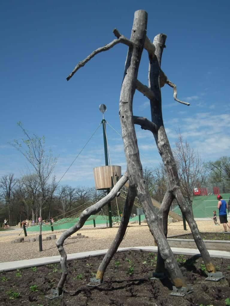 Whimsical ladders are hewn from tree branches in the snakes and ladders themed playground.