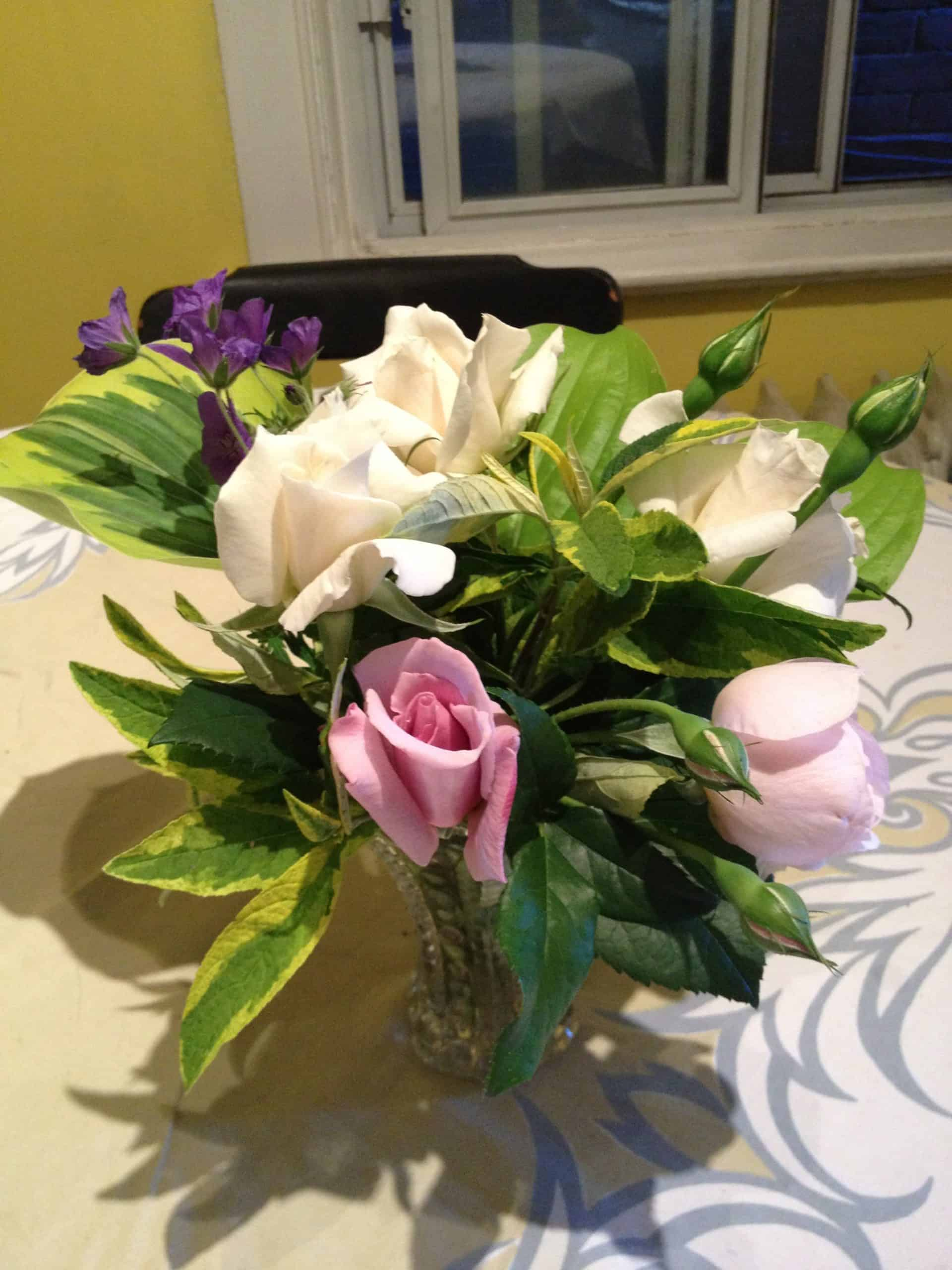 A classic flower arrangement ingredient, roses, mixed with some unconventional choices: hosta leaves, geraniums and variegated foliage from a butterfly bush.