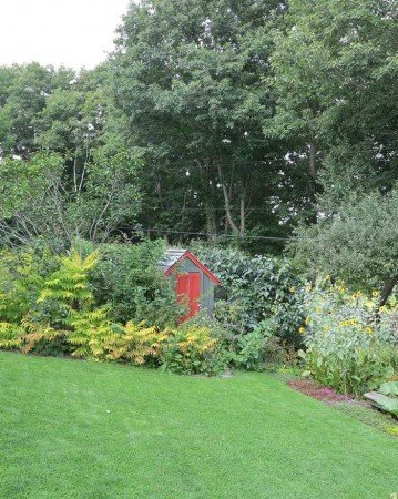 No need to hide or camouflage outbuildings if they're painted in complementary hues that blend with the surrounding landscape. This practical storage area serves as a focal point in Margaret Roach's garden in Copake Falls, N.Y. (Garden Making photo).